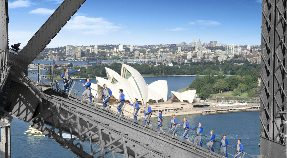 Group of people climbing the Sydney Harbour Bridge with Sydney Opera House in the background