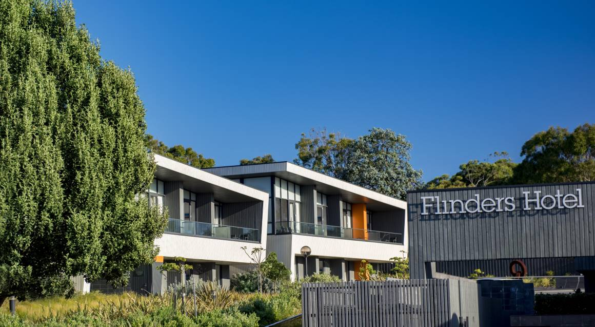 exterior of flinders hotel with trees and blue sky in the background