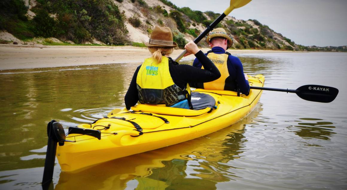 two people in a double kayak paddling in water