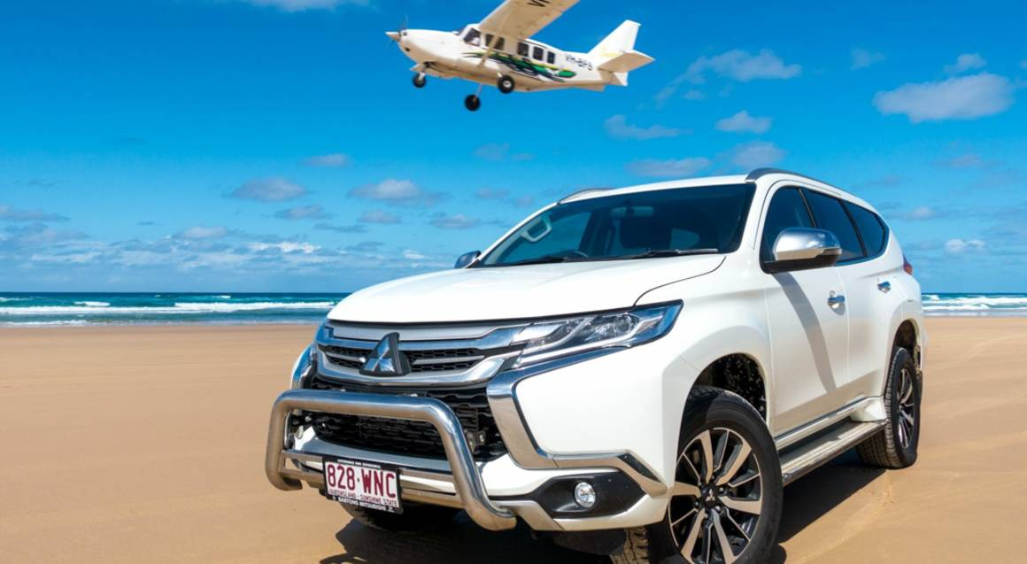 fraser island beach 4wd car and plane taking off