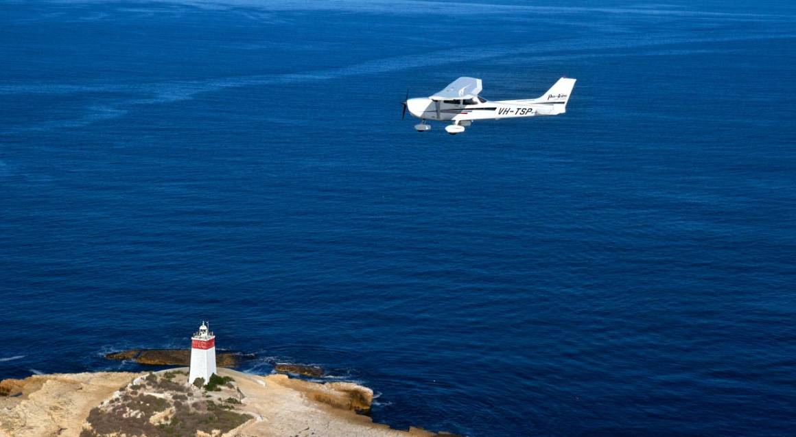 small white place flying over the ocean and lighthouse