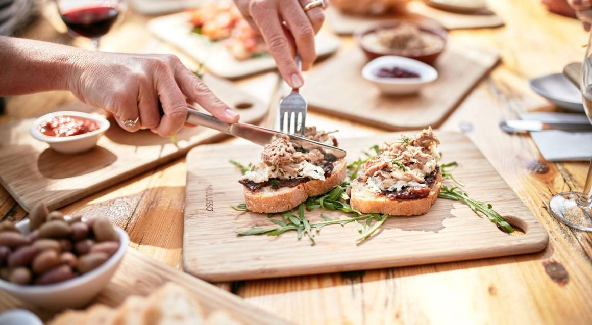 open sandwiches on wooden boards on a wooden table with a pair of hands cutting into one of the pieces of bread with a knife and fork