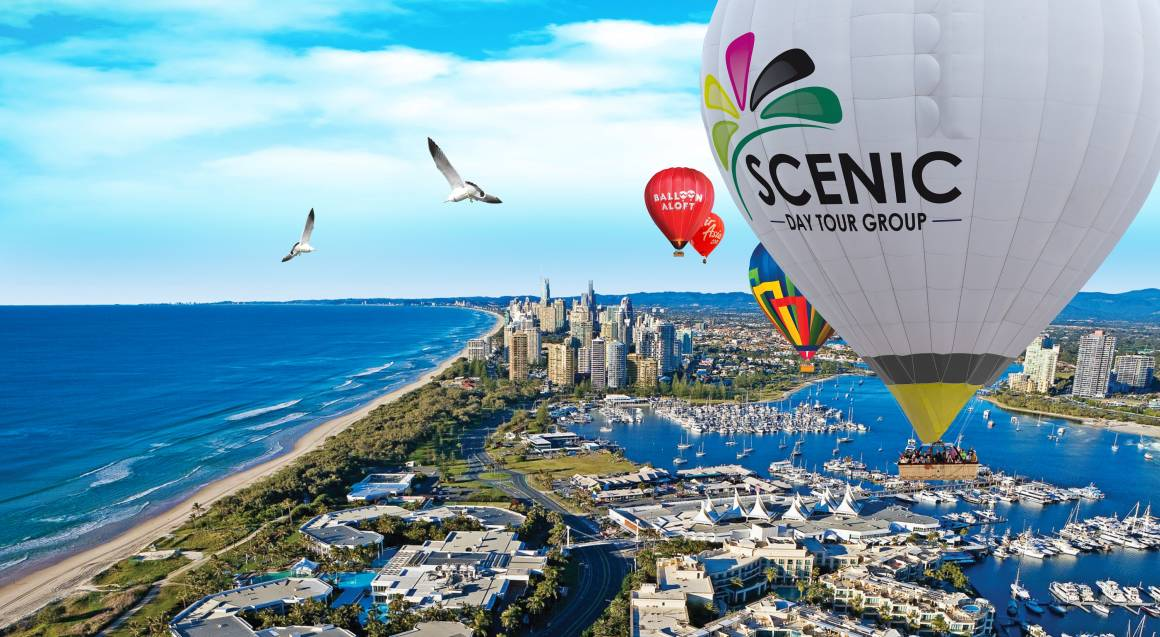 gold coast Multiple hot air balloons floating over city scape in blue sky background