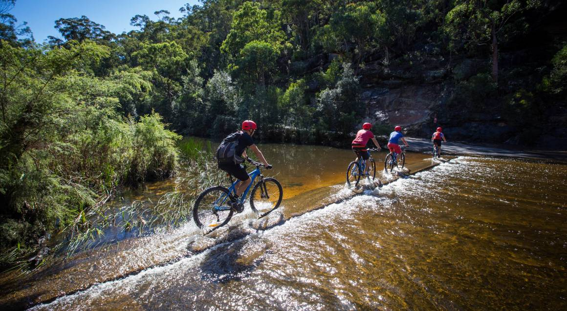 Mountain bike tour three riders riding their mountain bikes over a narrow cement track slightly covered with creek water the creek looks amber bushland in the background