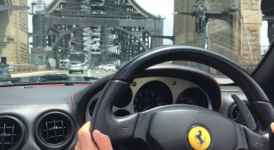 front of red ferrari 360 spider driving view over sydney harbour bridge