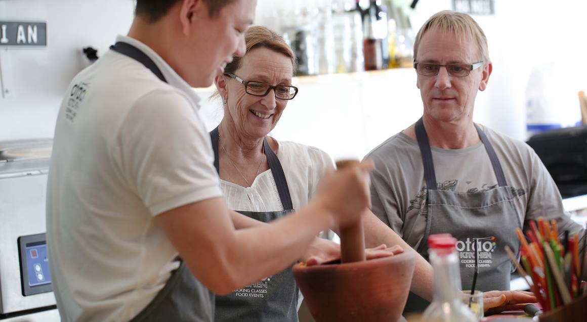 Otao kitchen chef showing couple how to ground spices