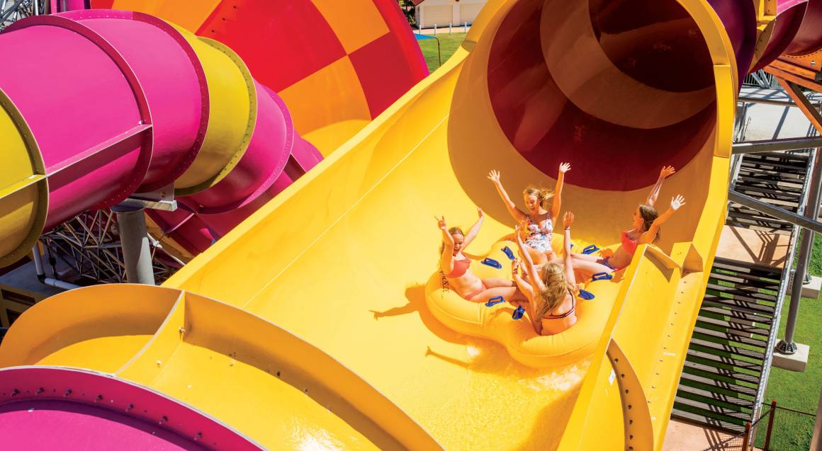 group of children sliding down a yellow water slide