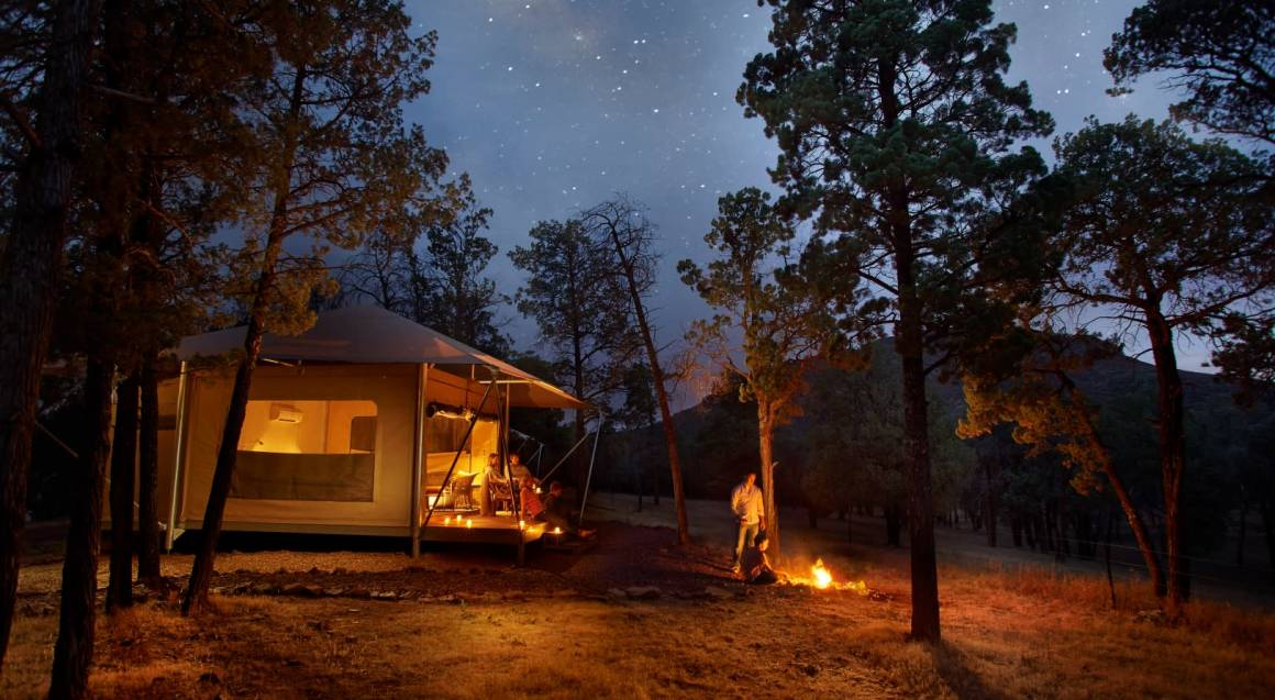 glamping tent with a woman sitting on the deck and a man standing at an open camp fire