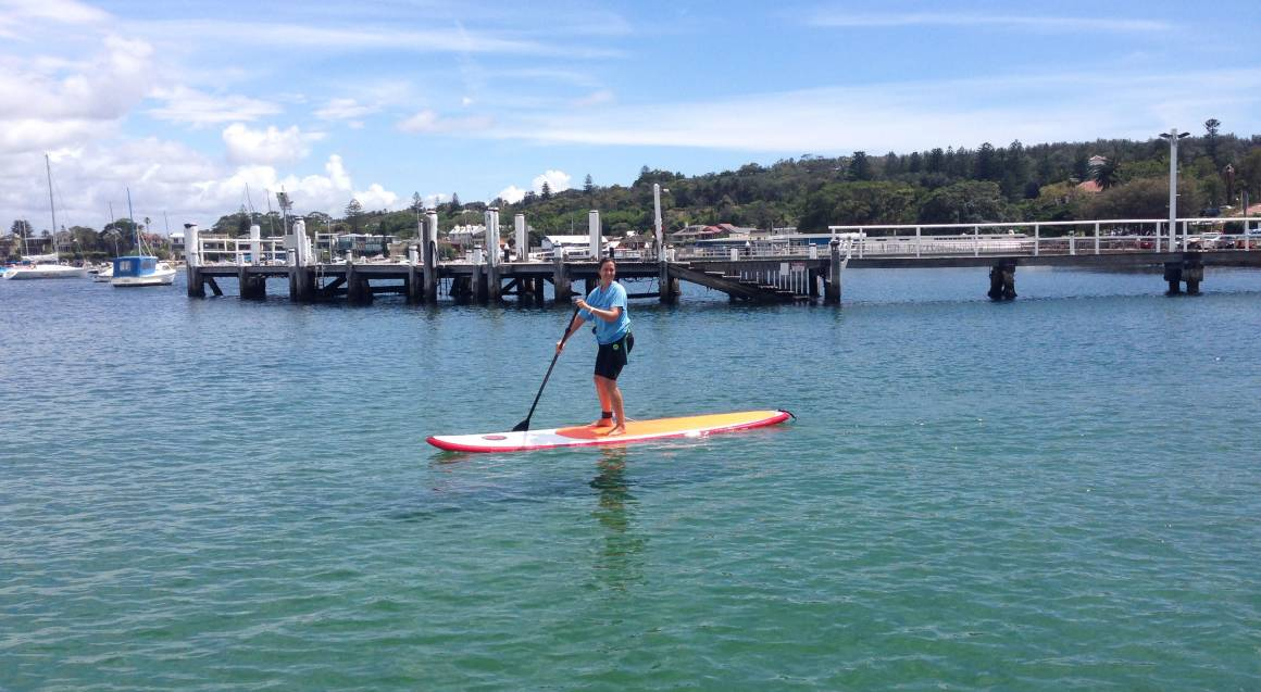 woman stand up paddle boarding on sydney harbour