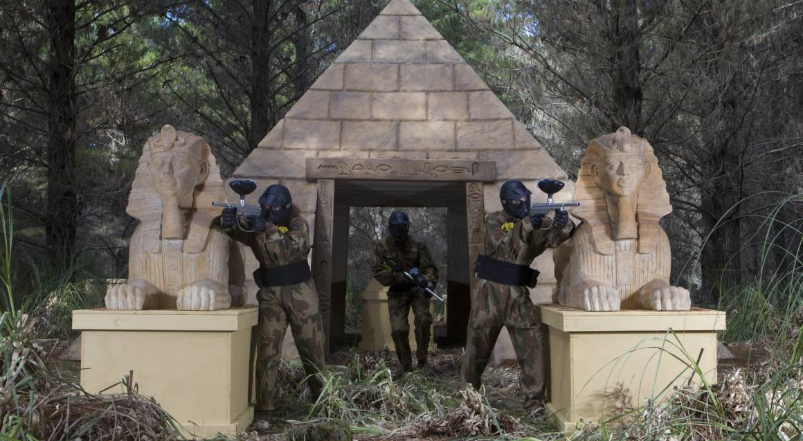 men playing paintball aiming guns egyptian setting