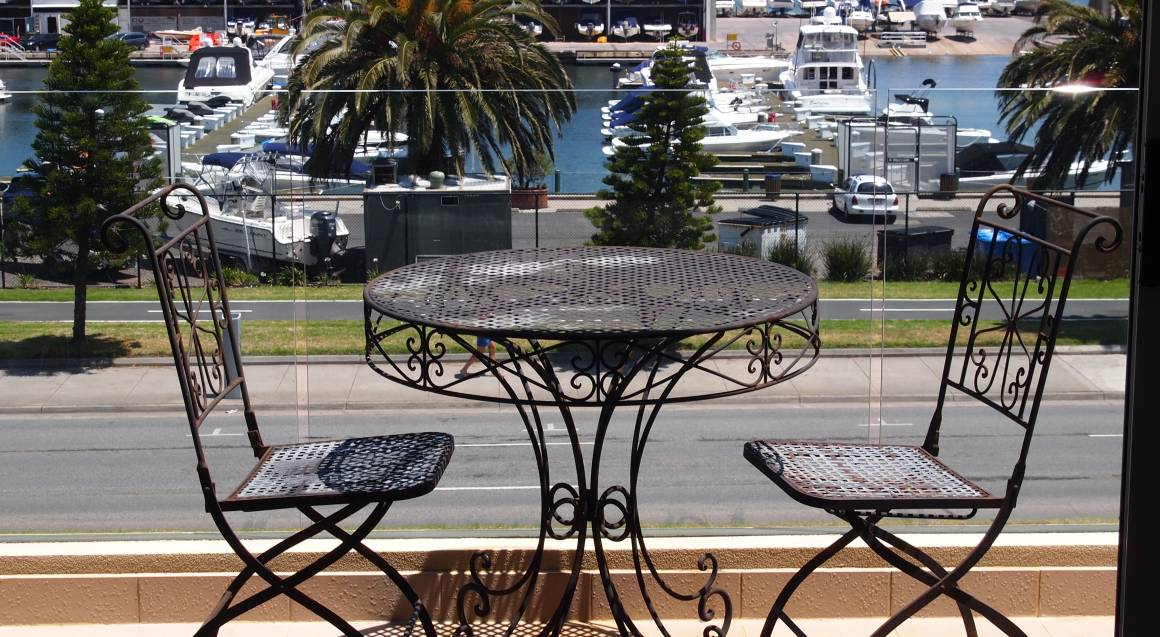 table and chairs on a balcony overlooking st kilda bay