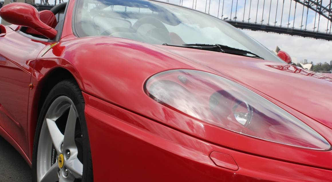 front of red ferrari 360 spider parked sydney harbour bridge