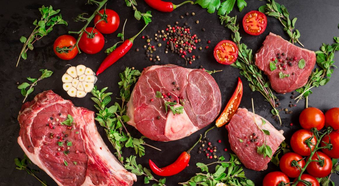 bbq cooking class range of meat raw styled on a black countertop styled with fresh red vegetables and herbs