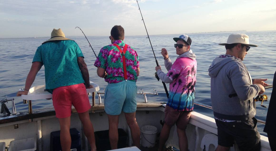 sport fishing charter trip group fishing on boat with ocean in background