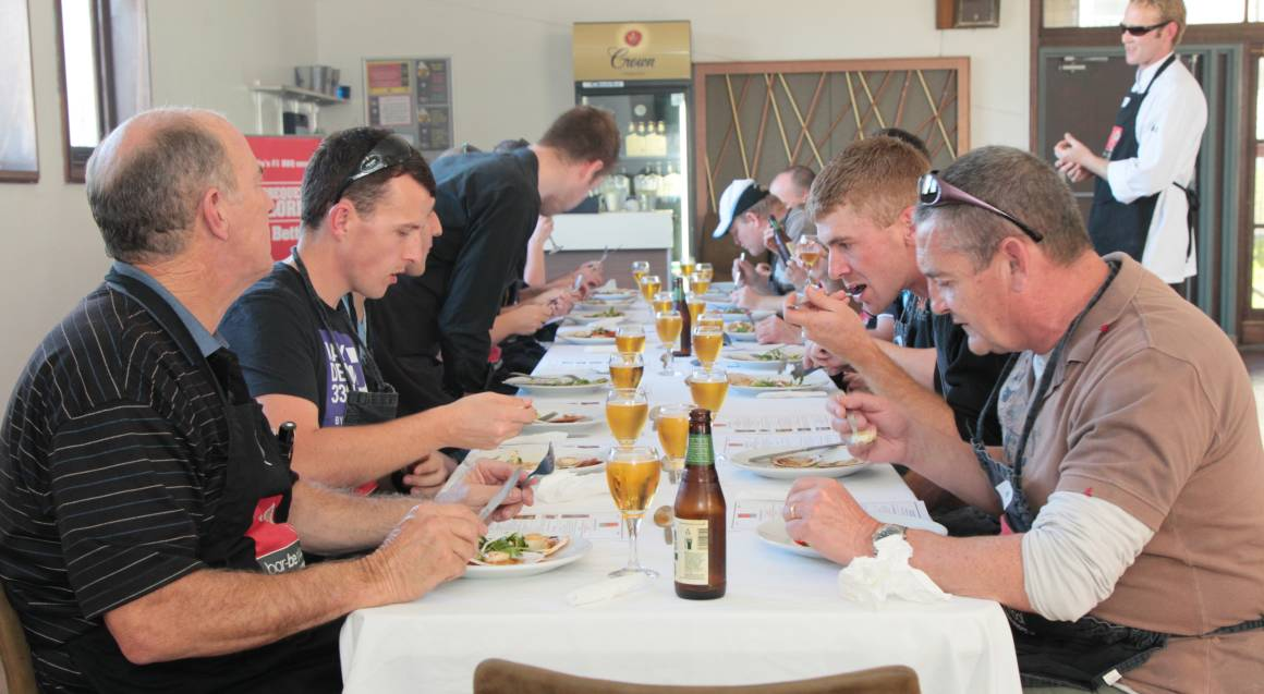 bbq cooking class long table of men eating bbq meats with glasses of beer at every setting