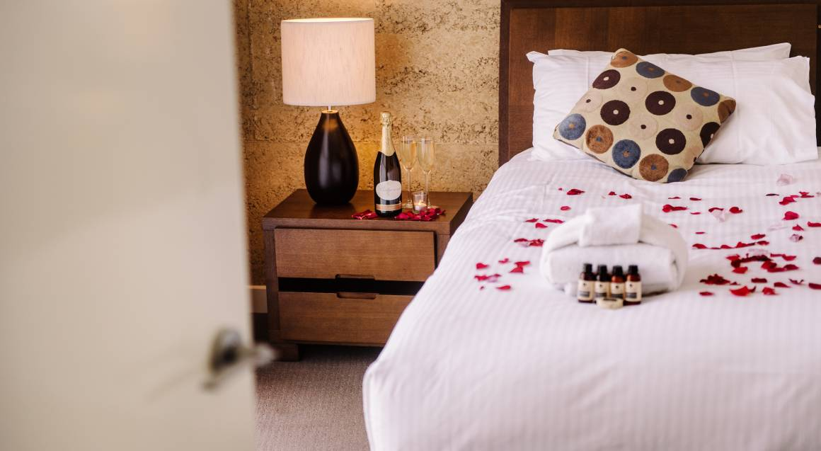 bed decorated with rose petals and a bottle of champagne on the table