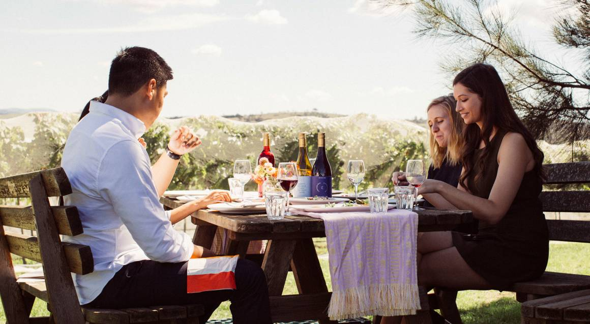 Contentious Character people eating lunch with wine vineyard table