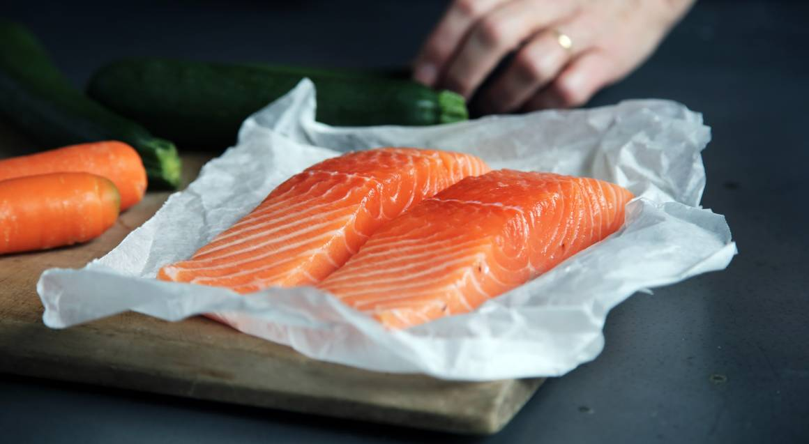 bbq cooking school bright orange salmon fillets sitting in paper on a bench with a hand in the background