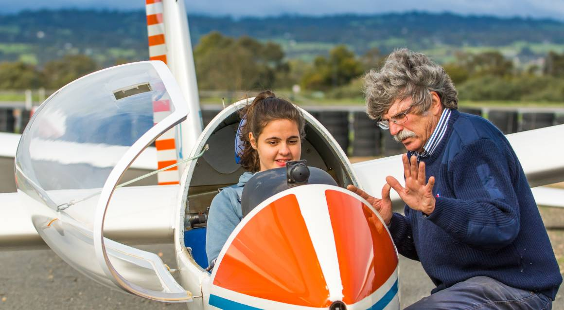 Pilot briefing woman in glider plane