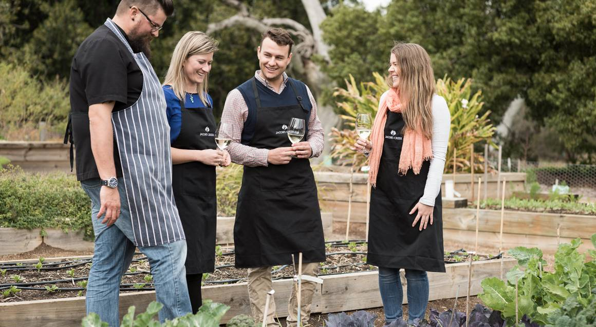 Group in kitchen garden looking at vegetables