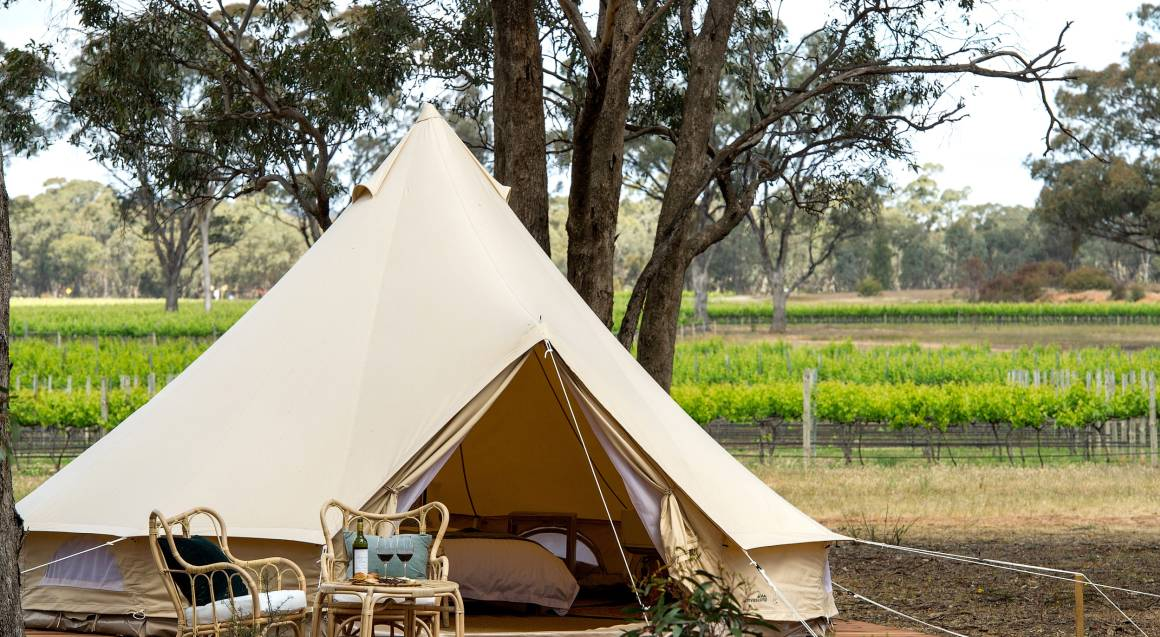 glamping tent set up in a winery with bottle of wine and glasses set up on the deck
