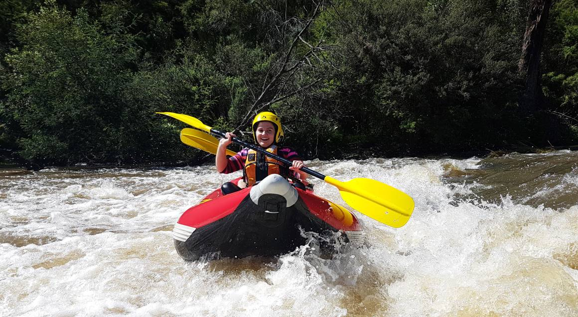 woman in a yellow helmet paddling through white water rapids on yarra river in a red raft