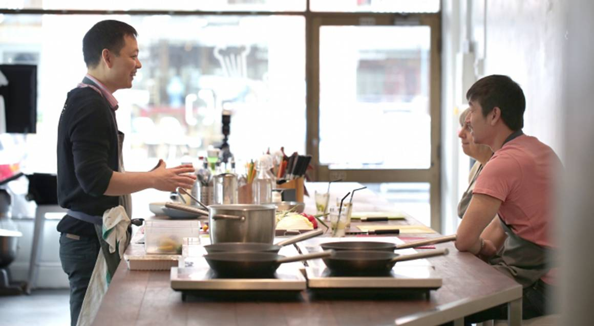 chef performing cooking demonstration in kitchen with couple