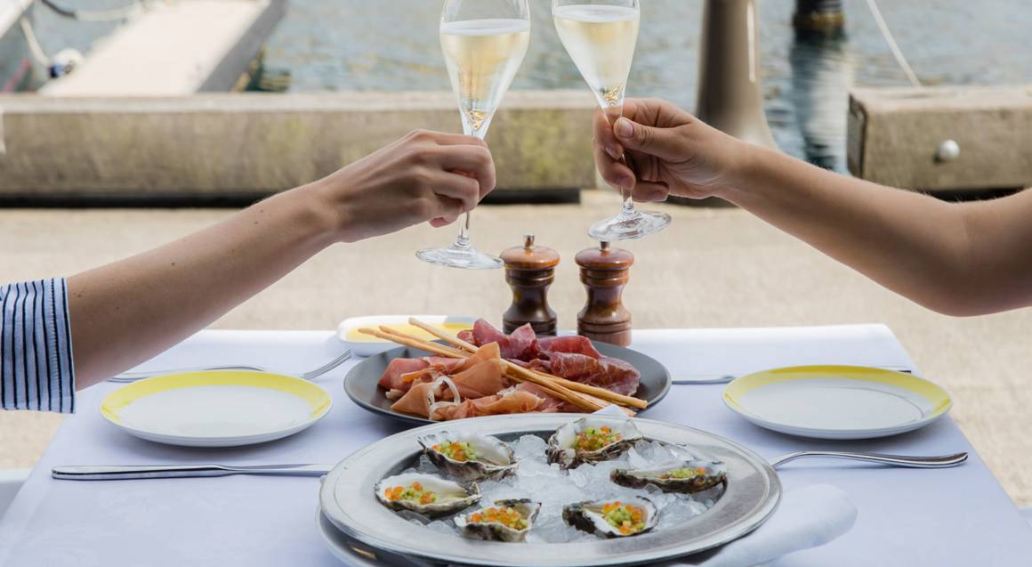 couple toasting with champagne over oysters and antipasto