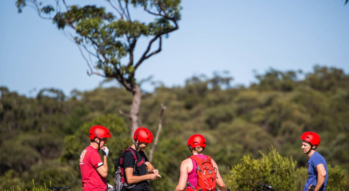 mountain bike tour group of people standing by their mountain bikes with red helmets on in bushland