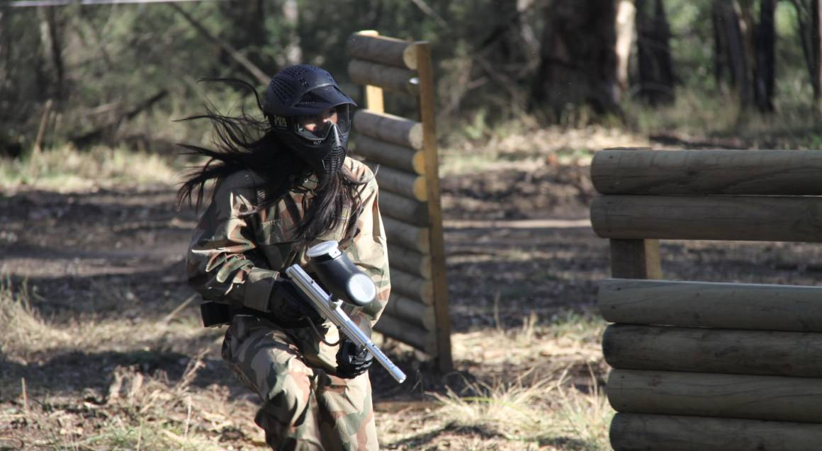 woman playing paintball on field