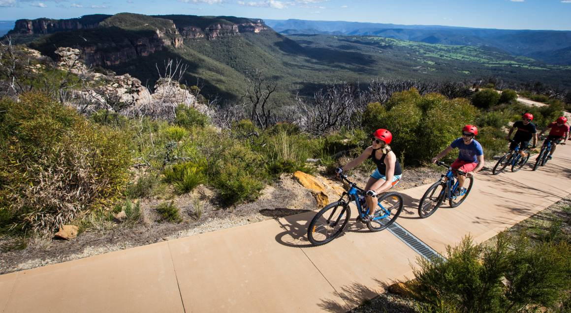Mountain bike tour group of mountain bike riders on a wide track with a valley and bushland in the background