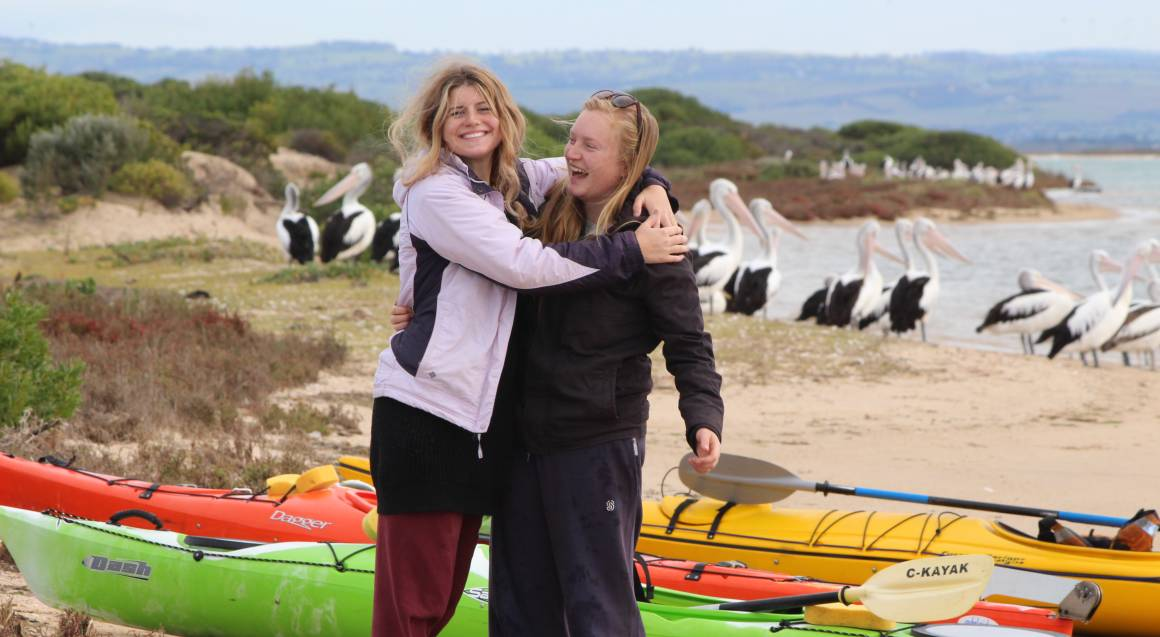two women hugging in front of kayaks on the beach with pelicans in the background