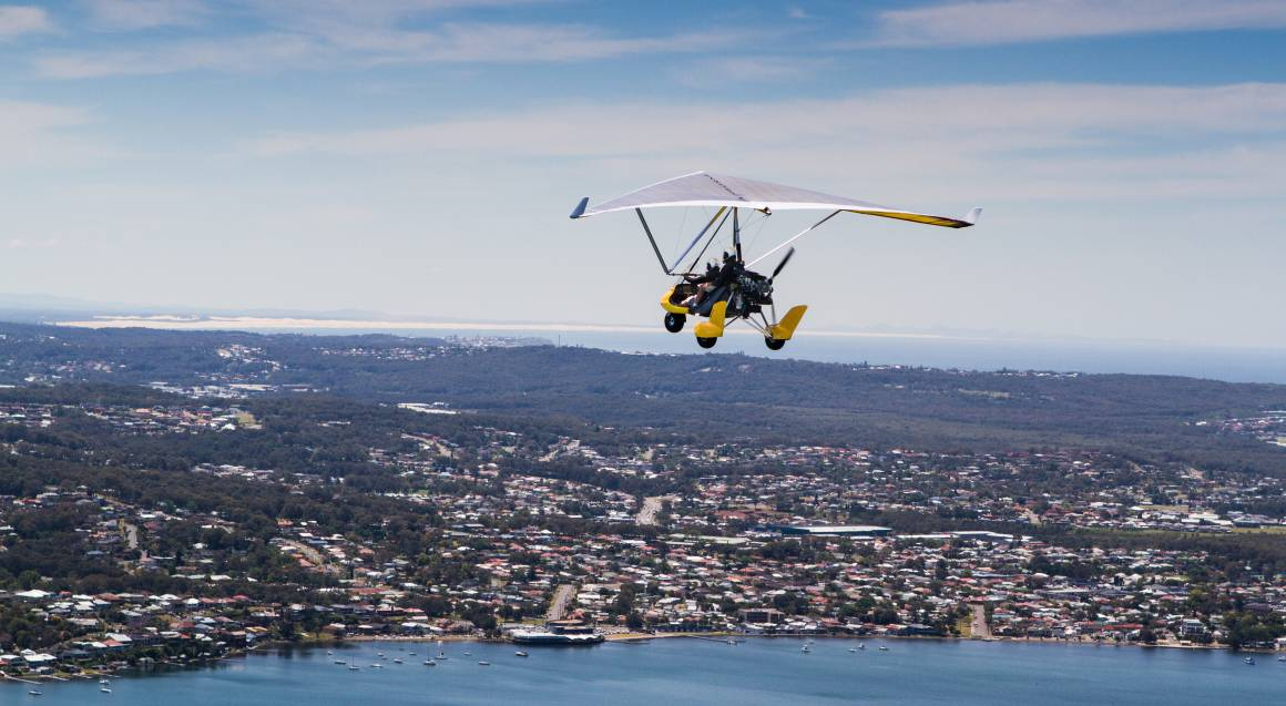 gyrocopter flying in the air with 2 passengers above the ocean and tiny buildings below