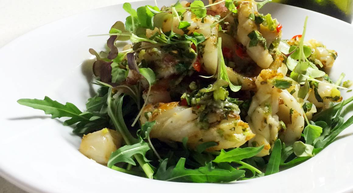 close up of bbq squid pieces in a salad of mostly green leaves