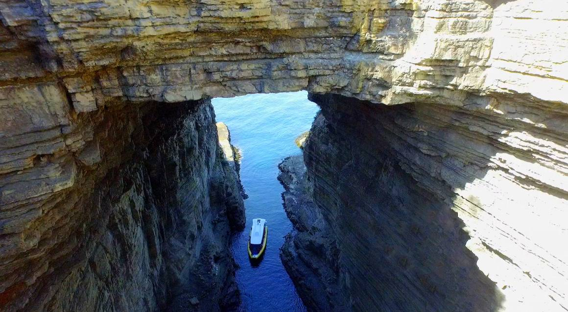boat sailing in through rocky arch off the coast of tasman penninsula