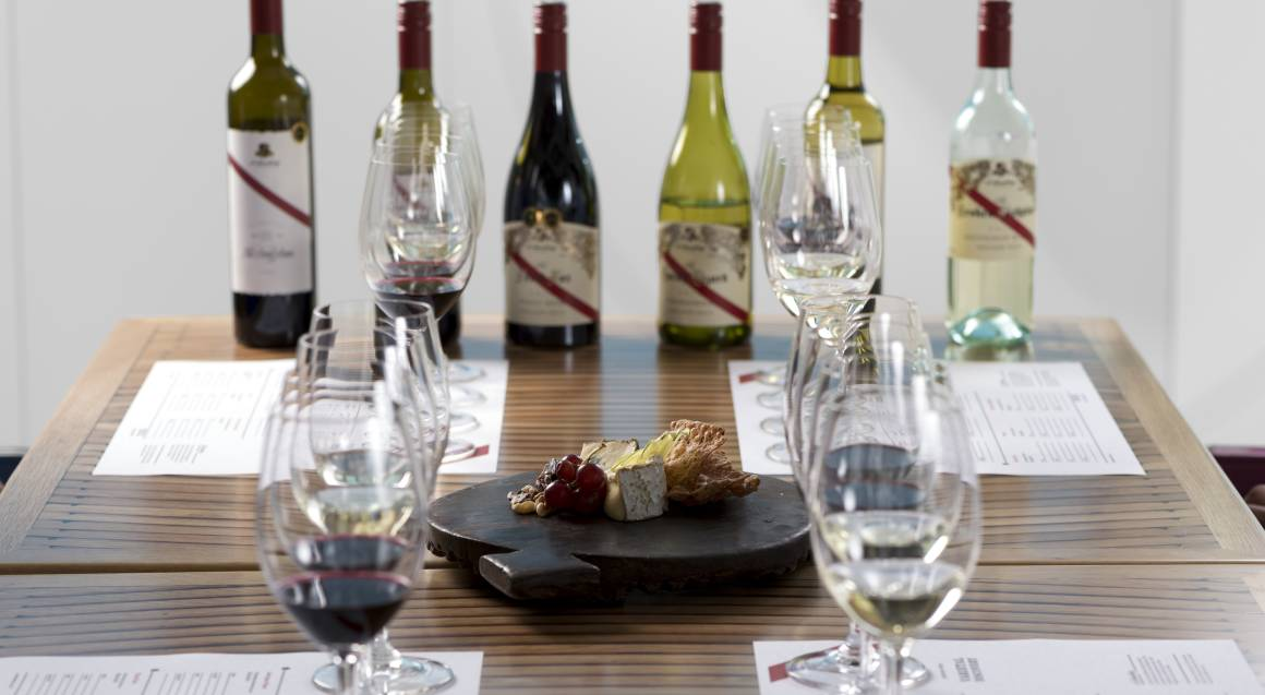 bottles of red and white wine with glasses set up at a table