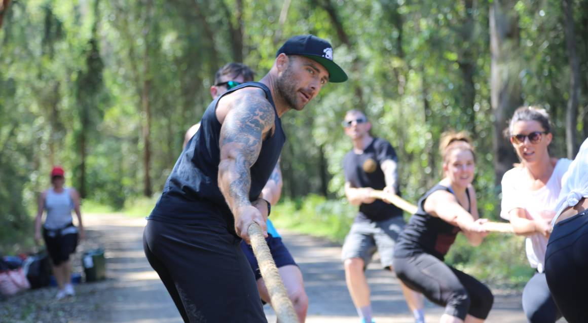 Commando steve personal trainer group training session on battle ropes doing tug-a-war