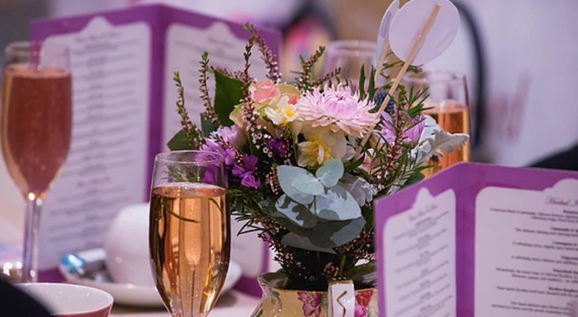 The Tea Salon high tea menu with champagne and floral table arrangement