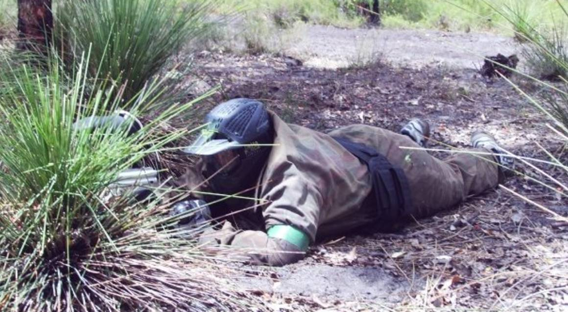 man playing paintball aiming gun on field laying down