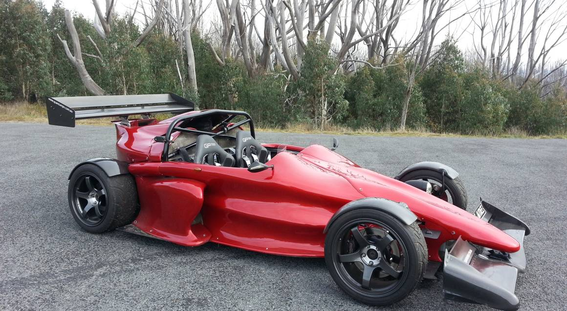 hypercar ride red high performance car with no roof with winter trees in background