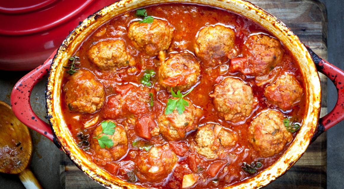 bbq cooking class casserole dish without the lid on filled with meat balls and vibrant red sauce garnished with green herbs