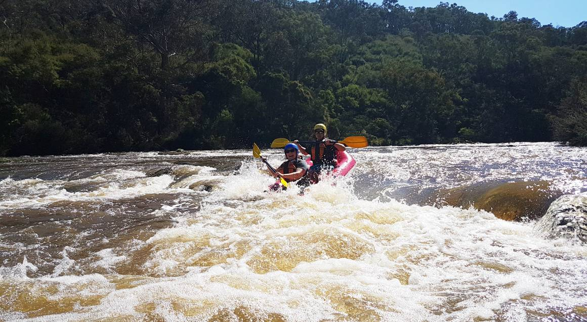 two people in a white water raft paddling through yarra river