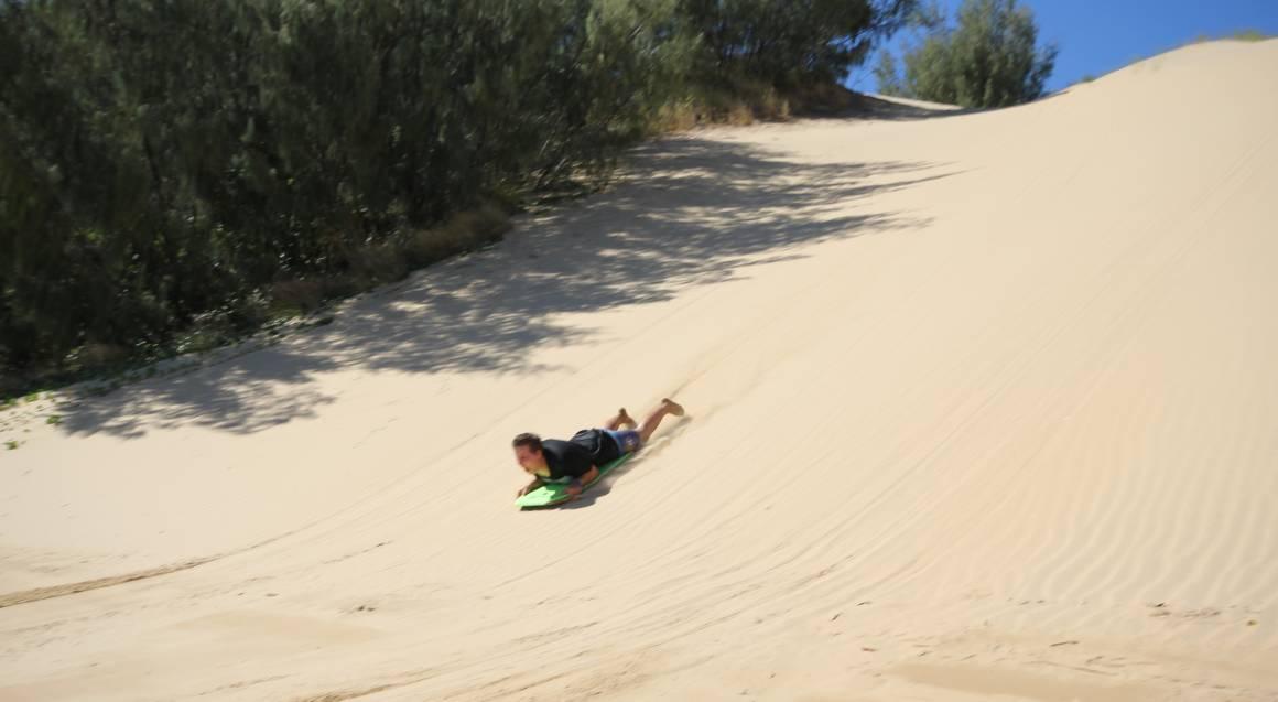 Man sandboarding on sand dunes