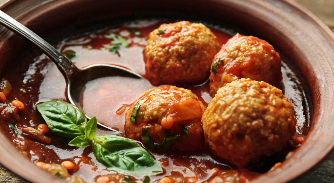 bbq cooking close of four meatballs in a soup with small round beans and herbs