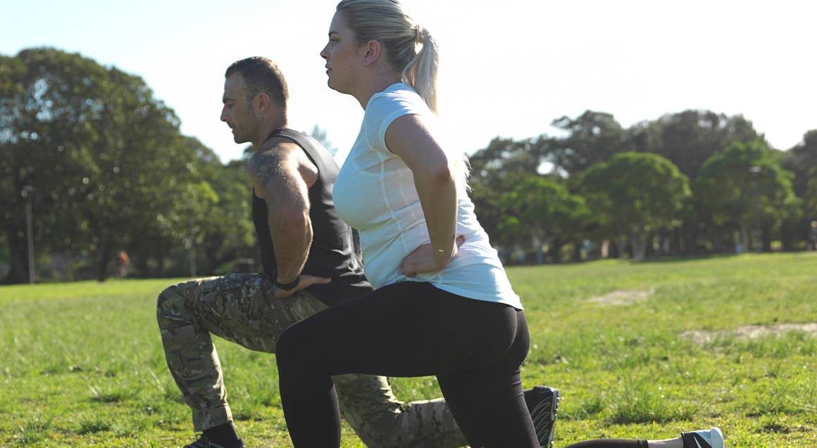 Commando steve personal trainer doing lunges in park with woman