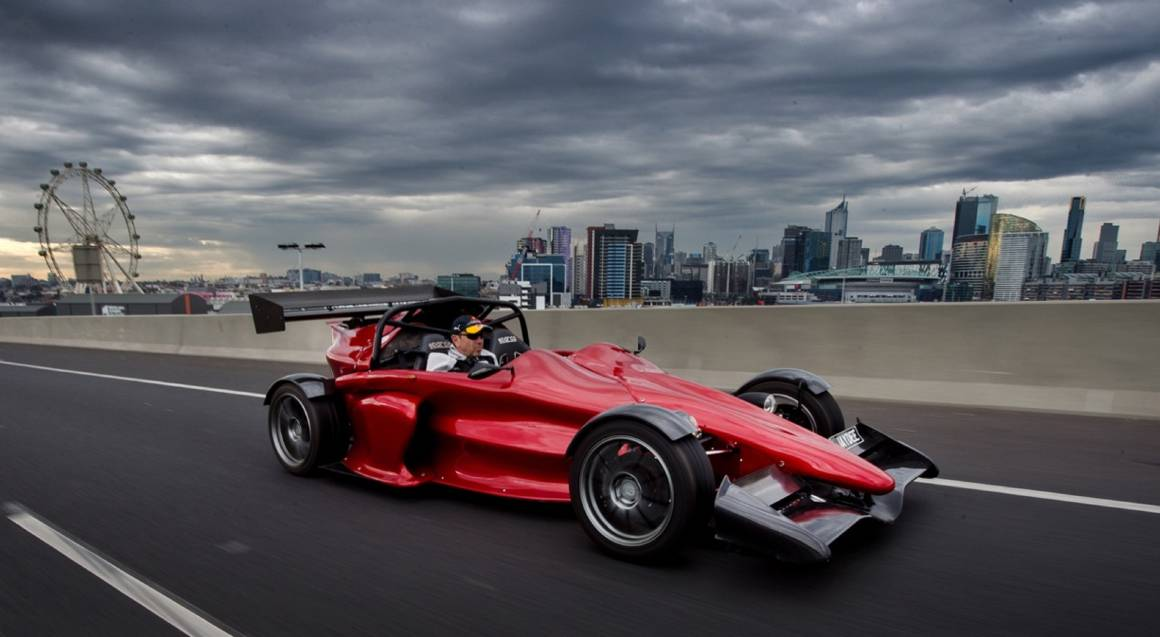 hypercar ride red high performance car with no roof driving down freeway with cloudy cityscape in background
