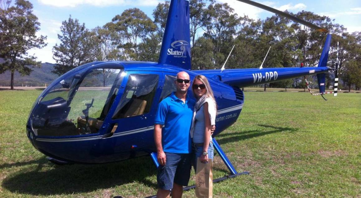 woman and man standing with helicopter
