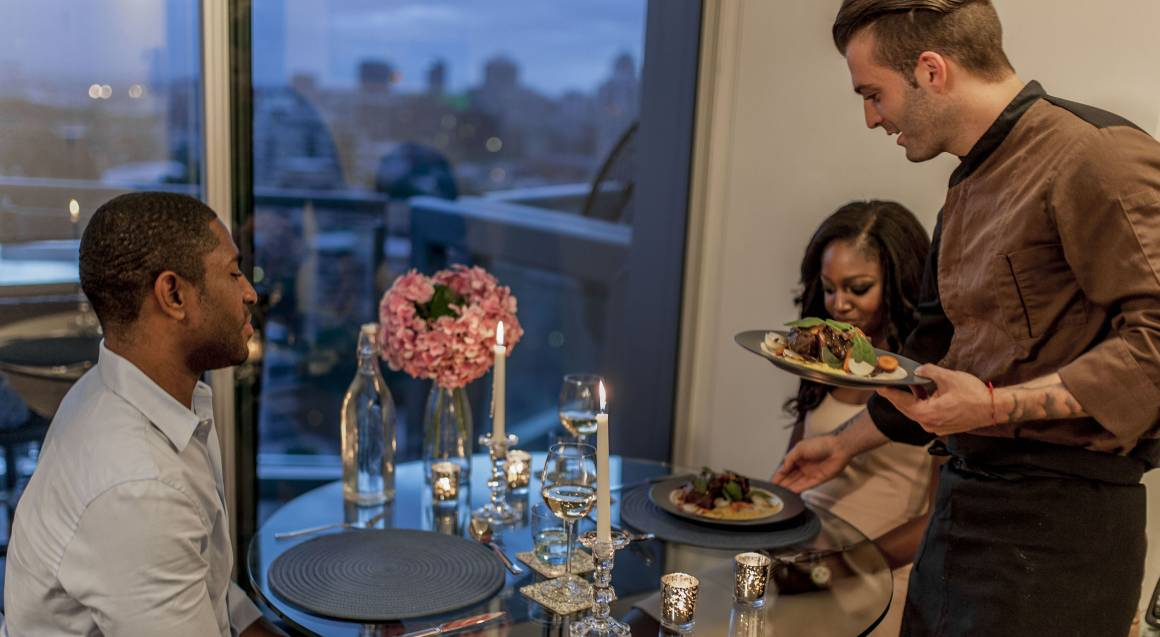 couple being served dinner at home cooked by private chef