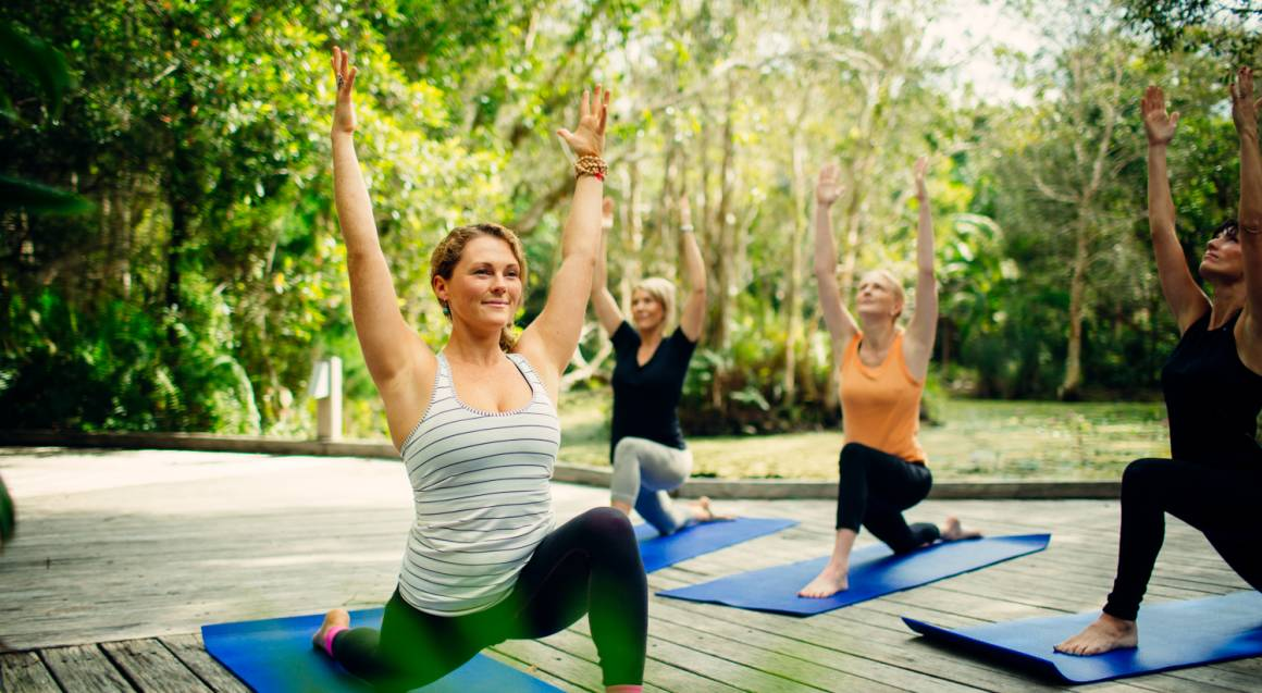 three women taking yoga class outside on deck surrounded by palm trees