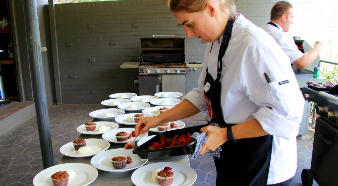 bbq cooking class woman in apron placing strawberries from a pan onto white plates with small cakes and ice cream on them